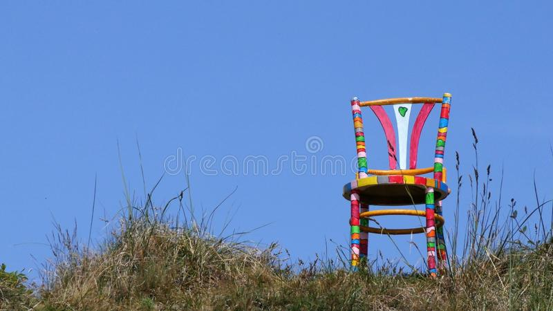 Colourful painted chair on top of dune royalty free stock image