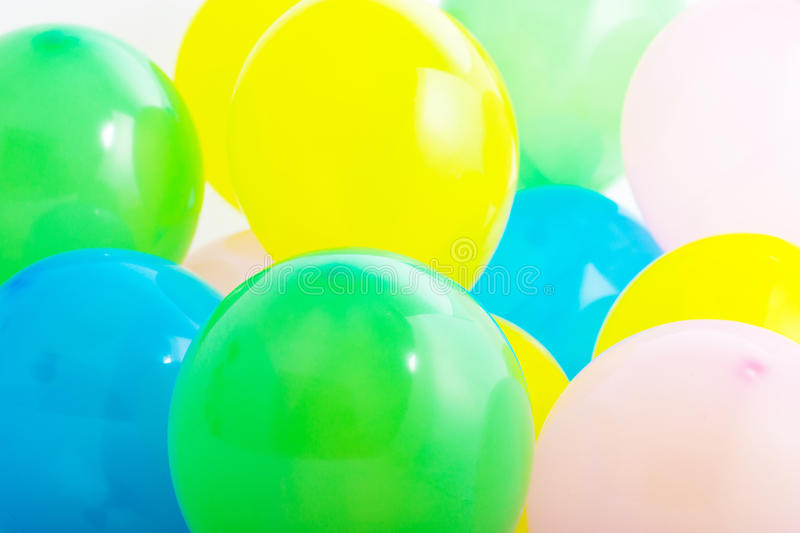 Colourful party balloons. Close up view of a bunch of colourful party balloons in yellow, blue, white and green for celebrating a birthday or festive occasion royalty free stock photography