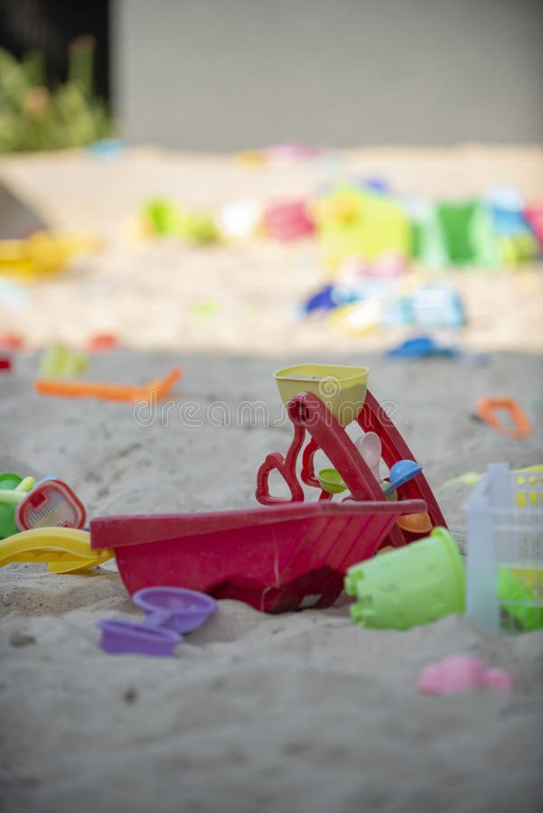 Colourful plastic toys with various shapes and kinds left unattended on a sand beach. stock images