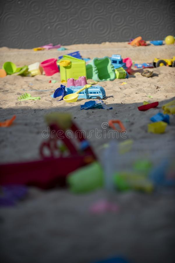 Colourful plastic toys with various shapes and kinds left unattended on a sand beach. royalty free stock photo