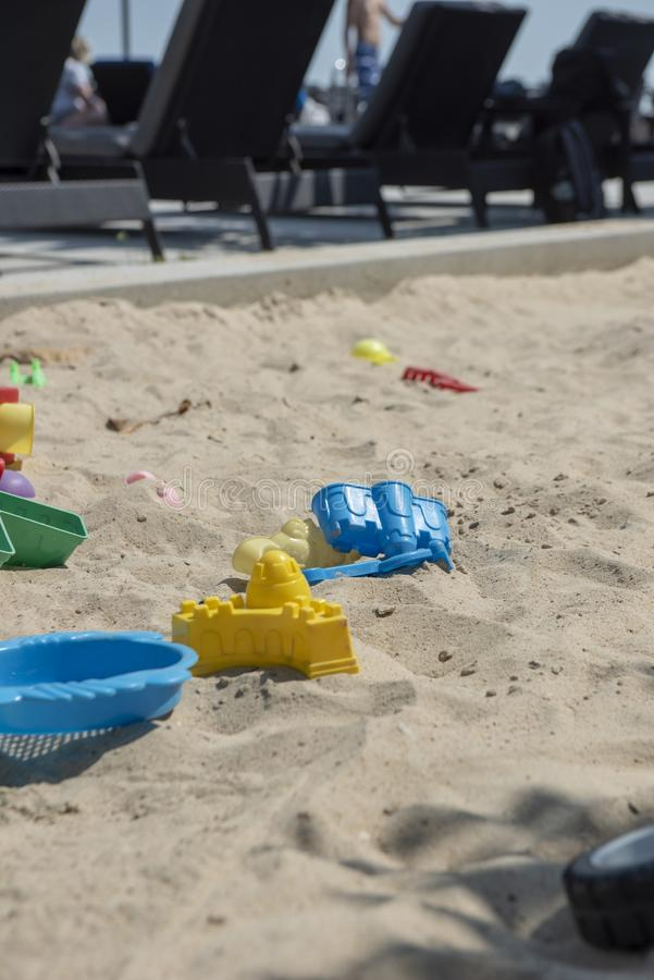 Colourful plastic toys with various shapes and kinds left unattended on a sand box in a resort. royalty free stock photos