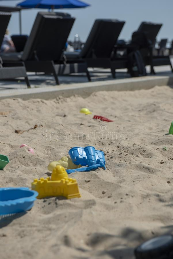 Colourful plastic toys with various shapes and kinds left unattended on a sand box in a resort. royalty free stock images
