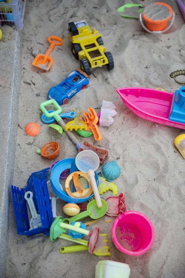 Colourful plastic toys with various shapes and kinds left unattended on a sand box in a resort. stock photo