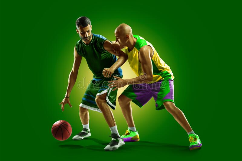Colourful professional basketball players isolated over green background stock photos