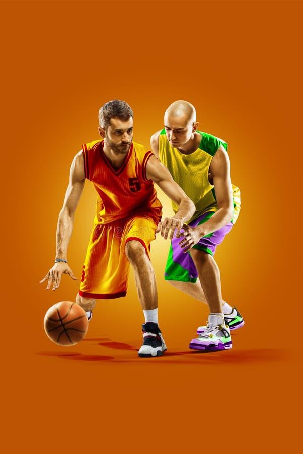 Colourful professional basketball players isolated over orange background royalty free stock image
