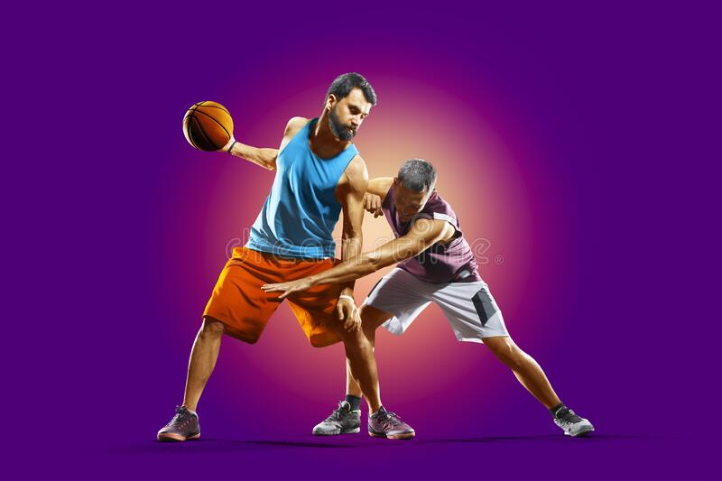 Colourful professional basketball players isolated over purple background royalty free stock photo