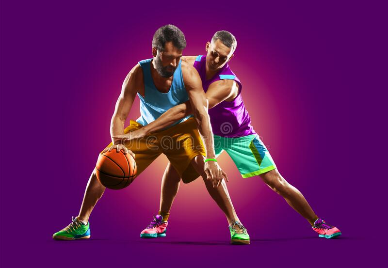 Colourful professional basketball players isolated over purple background royalty free stock photos
