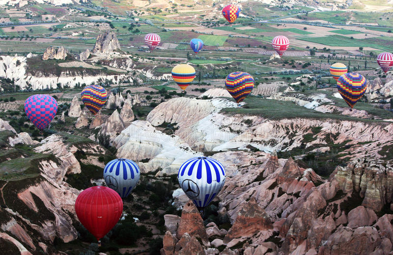 A colourful range of hot air balloons in Rose Valley in the Cappadocia region of Turkey. A colourful range of hot air balloons begin their journey at sunrise stock photos