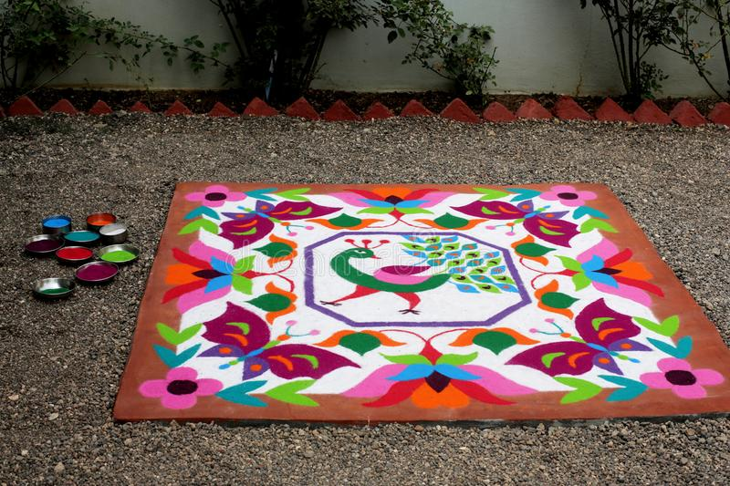 Colourful Rangoli Traditional Floral Design made with Dry Powdered Colours with Peacock, Flowers and Butterflies. A Colourful Rangoli Traditional Floral Design royalty free stock photo
