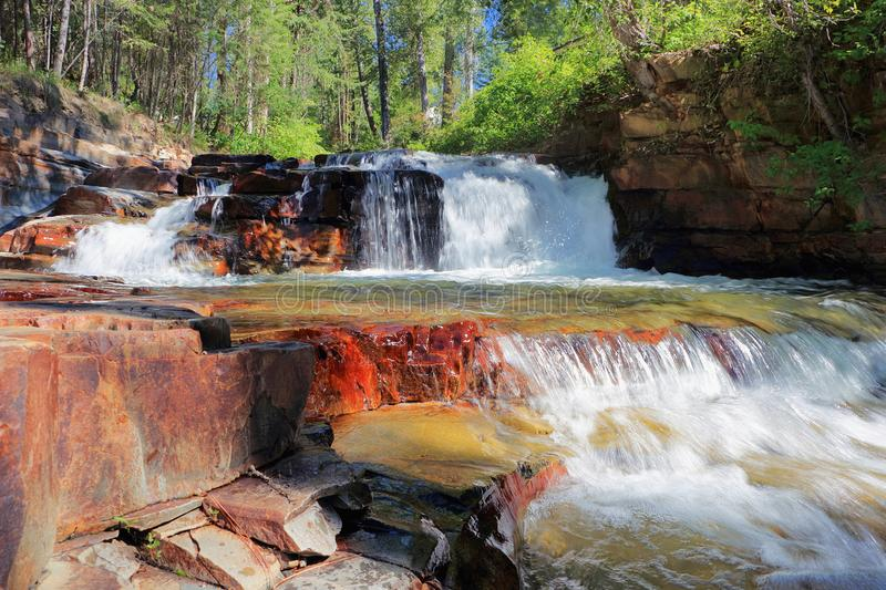 Colourful Cascades at Marysville Falls near Kimberley, British Columbia. Mark Creek is cascading over a number of beautiful smaller steps of red sandstone before royalty free stock images