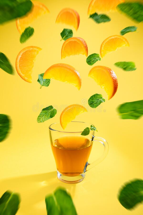 Colourful shot of orange fruit tea with orange slices and mint. Leafs swirling on warm yellow background stock image