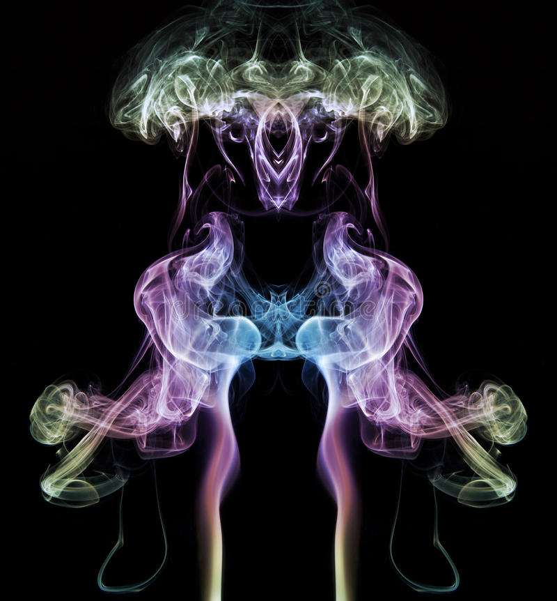 Colourful smoke art. Colourful symmetrical image of smoke art against a black background royalty free stock photography