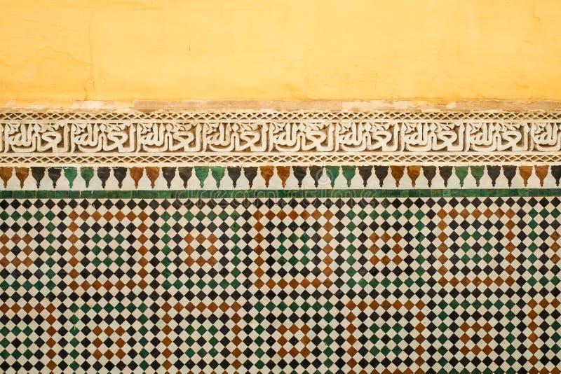 Colourful stary Marokański kolor żółty malował ścianę z zespołem Islamska kaligrafia nad zellige tilework obrazy stock