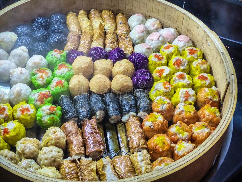 Colourful steamed dim sum at a street market stall in Malaysia. Malaysian street food - many colourful chinese dim sum being steamed in the traditional way at a royalty free stock photos