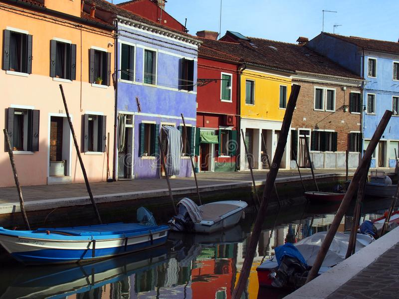 Colourful street in burano venice with moored boats on the canal royalty free stock images