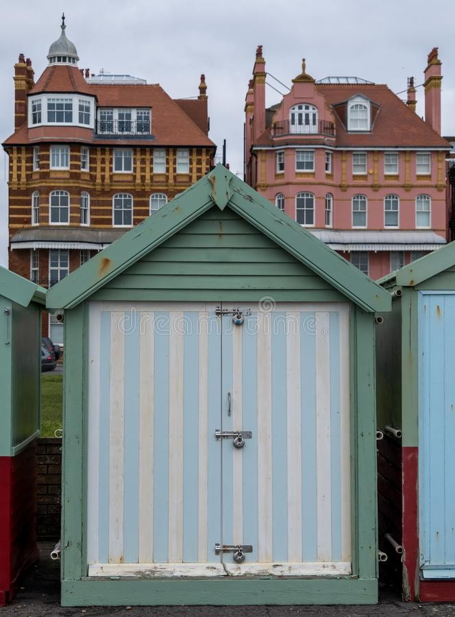 Colourful striped wooden beach hut on the sea front in Hove, Sussex, UK. Colourful wooden beach hut on the sea front in Hove, Sussex, UK with blocks of flats stock images