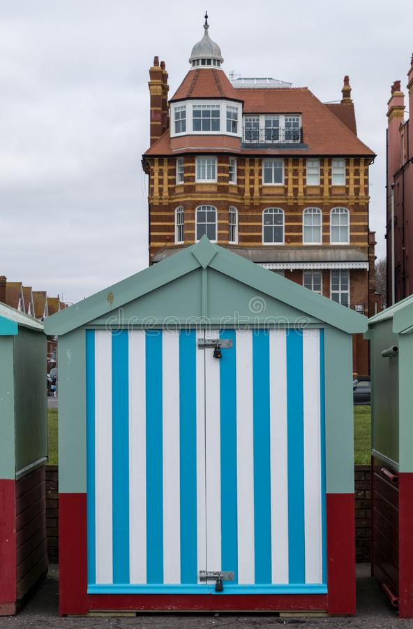 Colourful striped wooden beach hut on the sea front in Hove, Sussex, UK. Colourful wooden beach hut on the sea front in Hove, East Sussex, UK, with block of royalty free stock photography