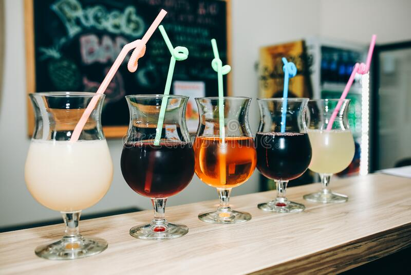 Colourful summer cocktails in glasses with straws. Drinks standing on the bar counter. Wine, pina colada and apple juice. Fresh stock image