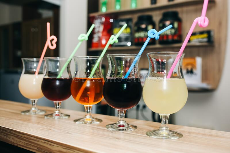 Colourful summer cocktails in glasses with straws. Drinks standing on the bar counter. Wine, pina colada and apple juice. Fresh. And cold for summer weather royalty free stock images