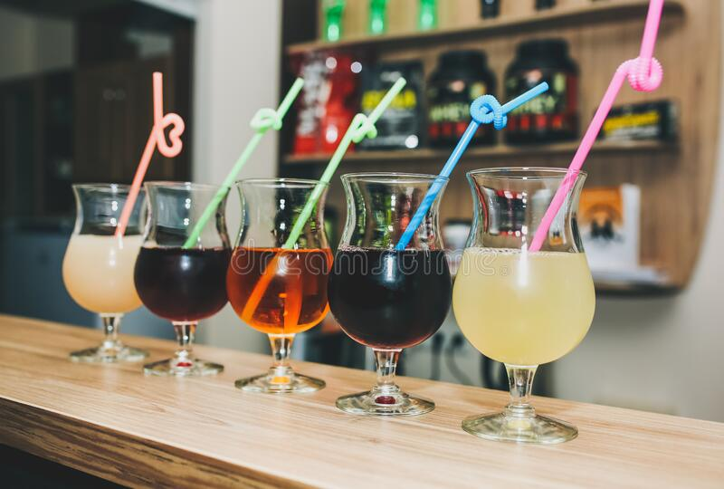 Colourful summer cocktails in glasses with straws. Drinks standing on the bar counter. Wine, pina colada and apple juice. Fresh. And cold for summer weather stock image