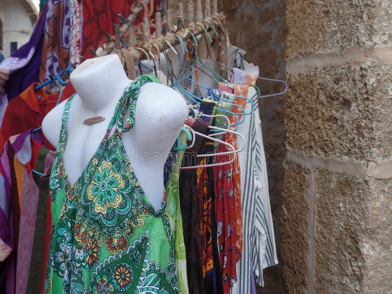 Colourful summer dresses for sale outside a clothes shop in Essaouira, Morocco stock photos