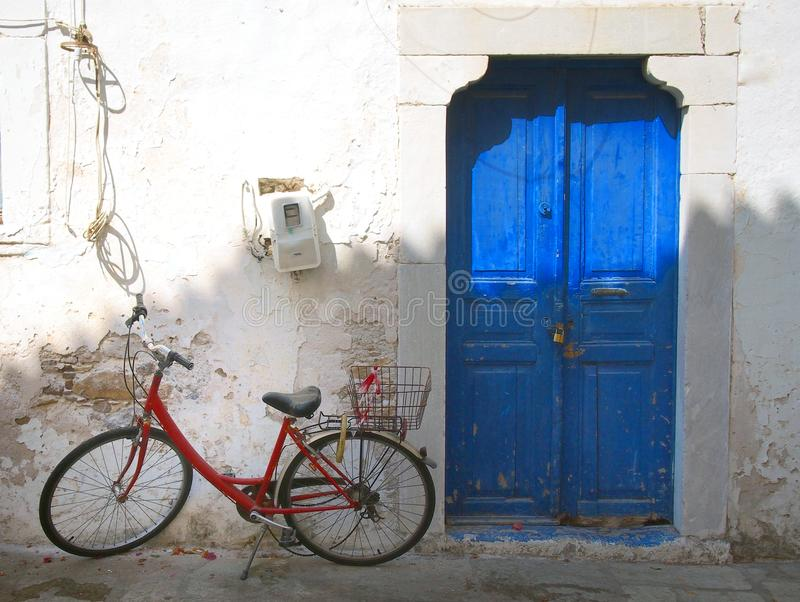 Colourful summer scene of an old red bike outside a greek house with whitewashed walls and a blue painted door in bright sunlight royalty free stock image
