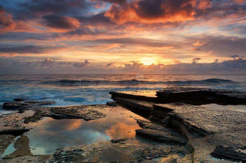 Colourful sunrise overlooking terrigal rock platform. A beautiful spring day with the waves crashing over terrigal rock platform. The colour in the clouds burst royalty free stock images