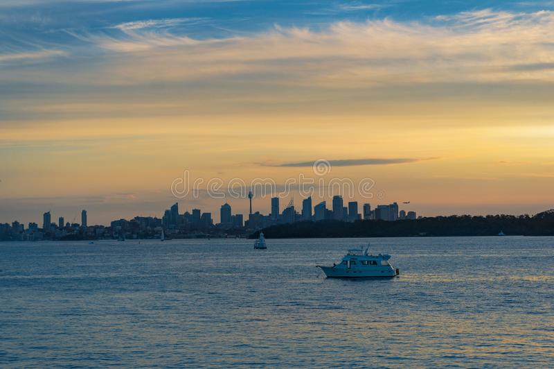 Colourful sunset over harbour with yachts and Sydey cityscape in the distance royalty free stock photos