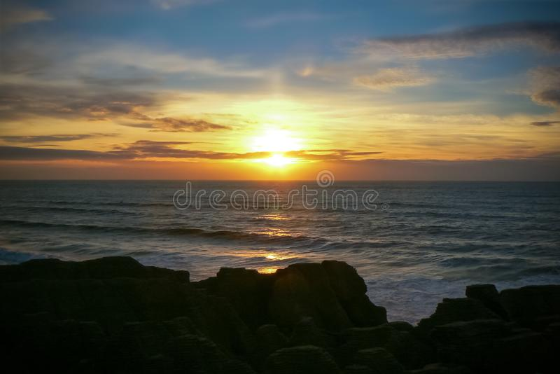 Colourful sunset over the sea at Punakaiki Pancake Rocks and Blowholes, New Zealand. Sunset in the Tasman Sea at Punakaiki Pancake Rocks and Blowholes, Paparoa royalty free stock image