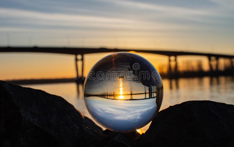 Clear globe in front of river and bridge. Colourful sunset with the river and bridge in the background of a clear globe. upside down reflection of background royalty free stock photos