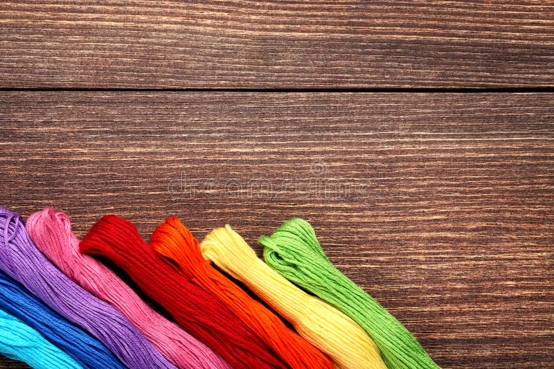Colourful threads. On brown wooden table stock photography