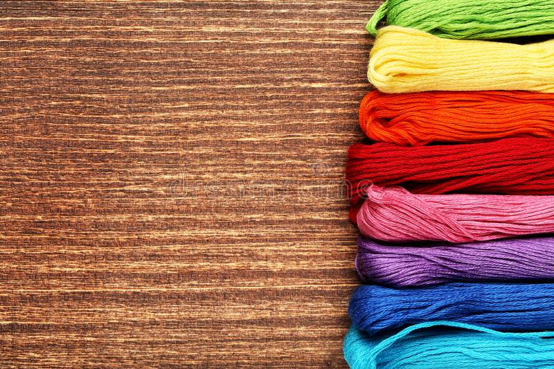 Colourful threads. On brown wooden table royalty free stock photo