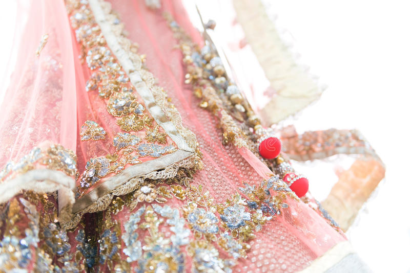 Colourful traditional indian bride dress. Closeup colourful traditional indian bride dress on white background. Selective focus stock photos