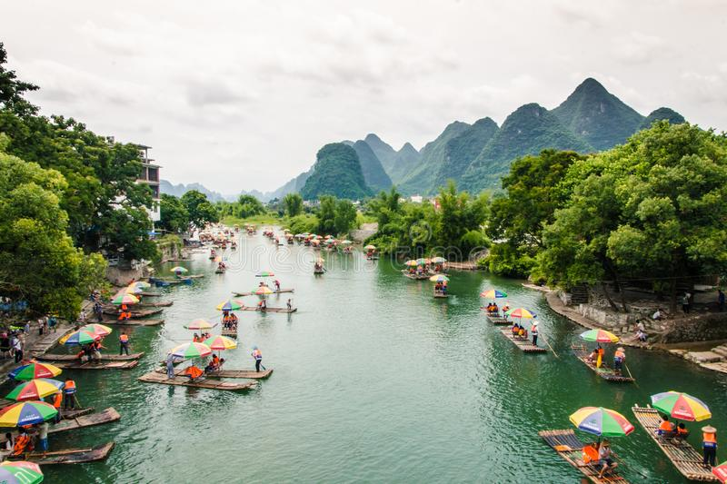 Rafts Cruising Along the Yulong River in Guilin, China. The colourful umbrellas from the many rafts traversing the Yulong River with the hilly landscape of stock photography