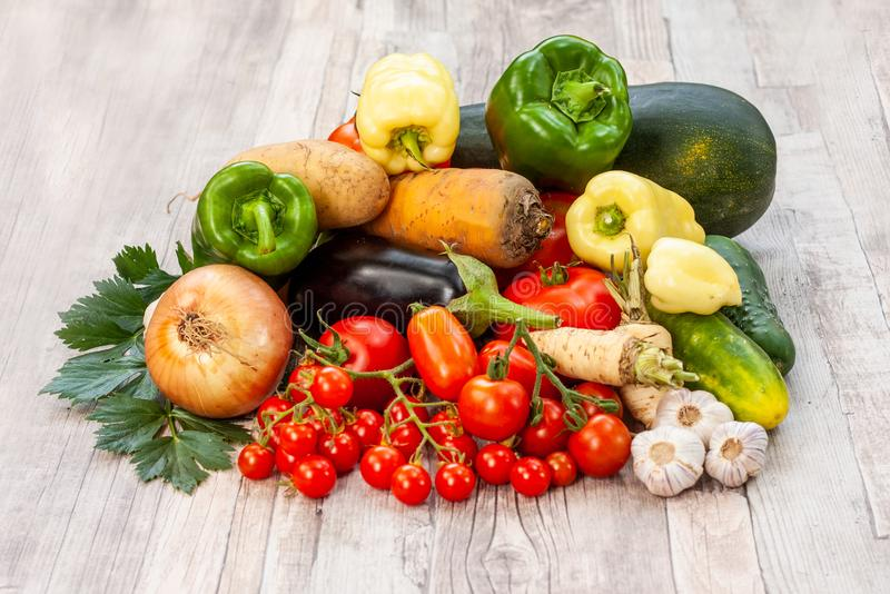 Colourful variety of fresh home grown vegetables. From an organic garden on a wooden surface. Tomato, green and yellow bell peppers, carrot, parsley, onion stock image