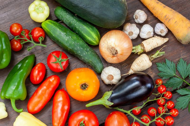Colourful variety of fresh home grown vegetables. From an organic garden on a wooden surface. Tomato, green and yellow bell peppers, carrot, parsley, onion royalty free stock photography
