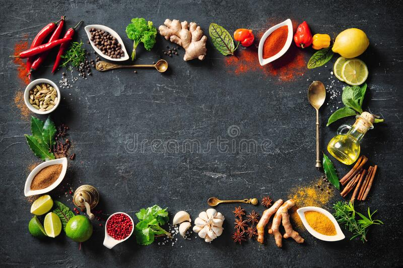 Colourful various herbs and spices for cooking on dark background stock photos