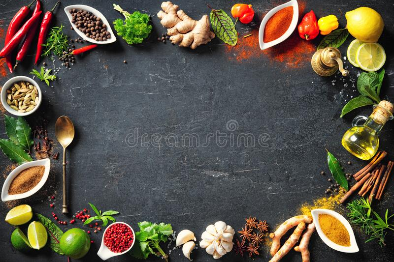 Colourful various herbs and spices for cooking on dark background royalty free stock photography