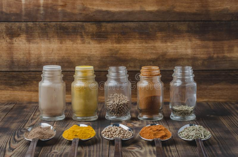 Colourful various spices in spoons and in glass jars on a wooden table. Cooking background. Food, seasoning, ingredient, cuisine, top, powder, dry, indian stock photo