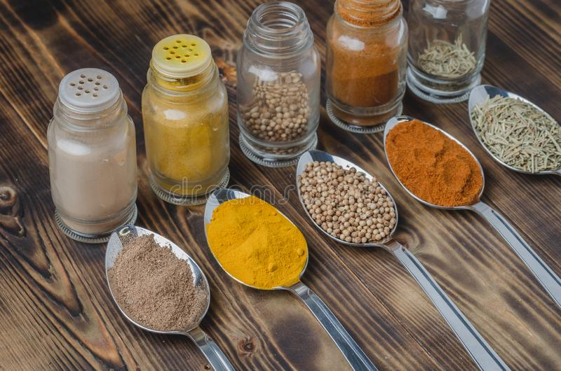 Colourful various spices in spoons and in glass jars on a wooden table. Cooking background. Food, seasoning, ingredient, cuisine, top, powder, dry, indian stock image