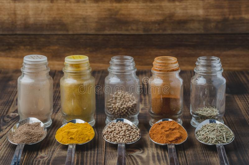 Colourful various spices in spoons and in glass jars on a wooden table. Cooking background. Food, seasoning, ingredient, cuisine, top, powder, dry, indian royalty free stock photography