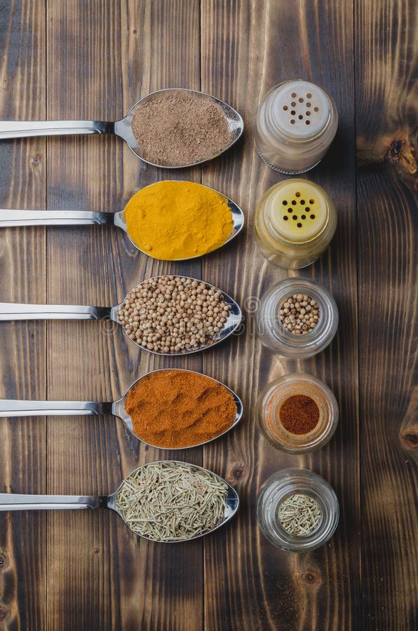 Colourful various spices in spoons and in glass jars on a wooden table. Top view. Cooking background. Food, seasoning, ingredient, cuisine, powder, dry, indian stock photos