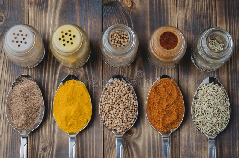 Colourful various spices in spoons and in glass jars on a wooden table. Top view. Cooking background. Food, seasoning, ingredient, cuisine, powder, dry, indian royalty free stock image