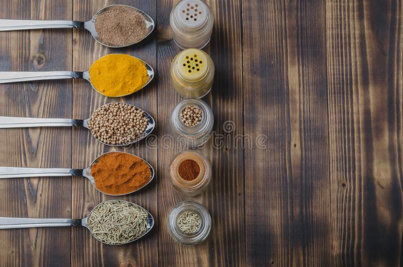 Colourful various spices in spoons and in glass jars on a wooden table. Top view and copyspace. Cooking background. Food, seasoning, ingredient, cuisine royalty free stock photography