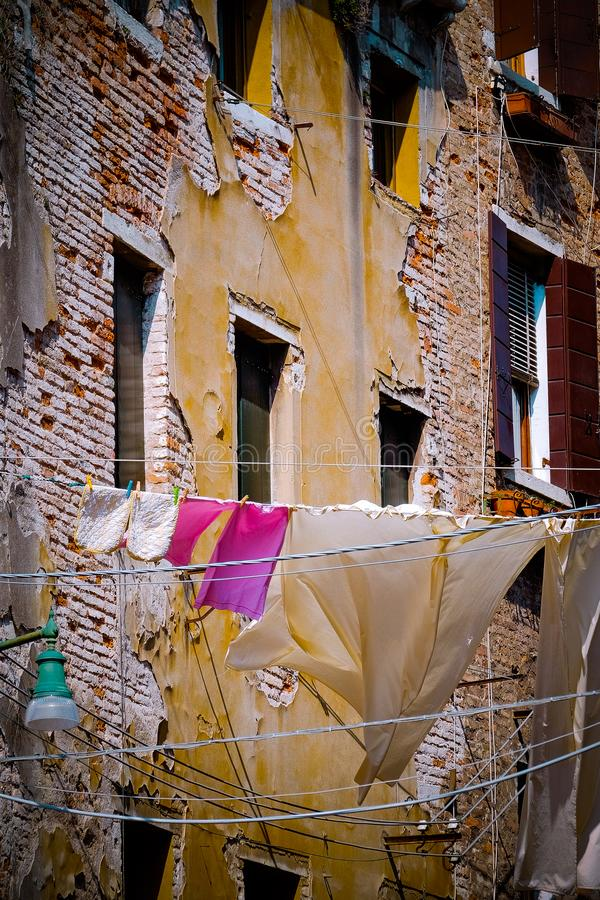 Washing hanging out windows of old building stock image