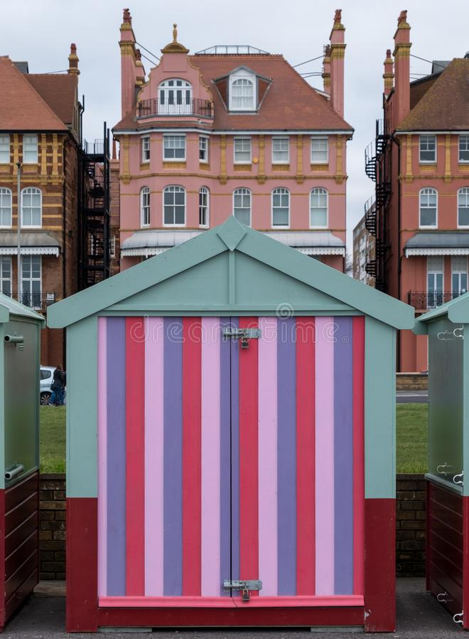 Colourful wooden beach hut on the sea front in Hove, Sussex, UK. Colourful wooden beach hut in candy stripes on the sea front in Hove, East Sussex, UK with royalty free stock photography