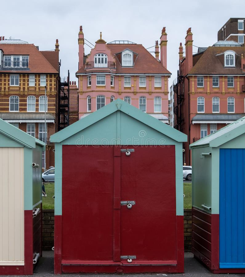 Colourful wooden beach hut on the sea front in Hove, Sussex, UK. Colourful wooden beach hut on the sea front in Hove, Sussex, UK with blocks of flats behind royalty free stock images