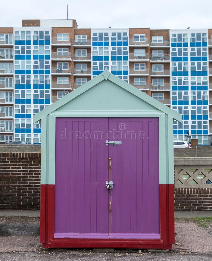 Colourful wooden beach hut on the sea front in Hove, Sussex, UK. Colourful wooden beach hut on the sea front in Hove, Sussex, UK with block of flats behind royalty free stock photos