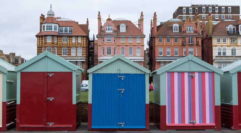 Colourful wooden beach huts on the sea front in Hove, Sussex, UK. Colourful wooden beach huts on the sea front in Hove, East Sussex, UK, with blocks of flats royalty free stock photography