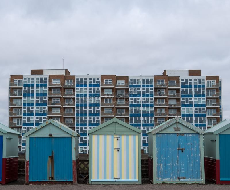 Colourful wooden beach huts on the sea front in Hove, Sussex, UK. Colourful wooden beach huts on the sea front in Hove, Sussex, UK with block of flats behind royalty free stock photo